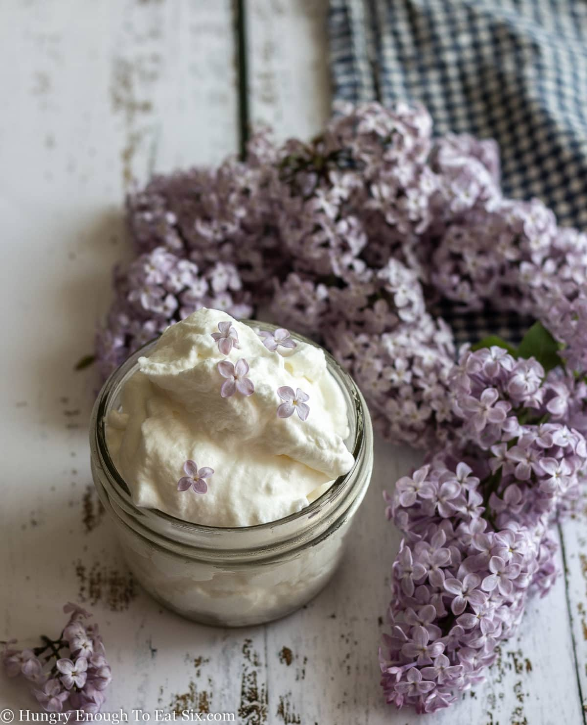 Jar of whipped cream and sprigs of lilacs laying on a white wooden surface.