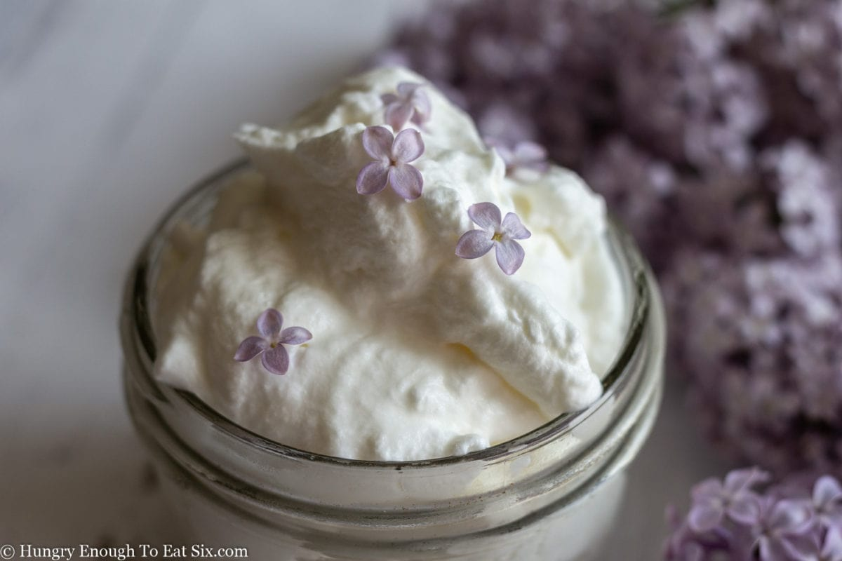 Whipped cream with lilac flowers on top and in background.