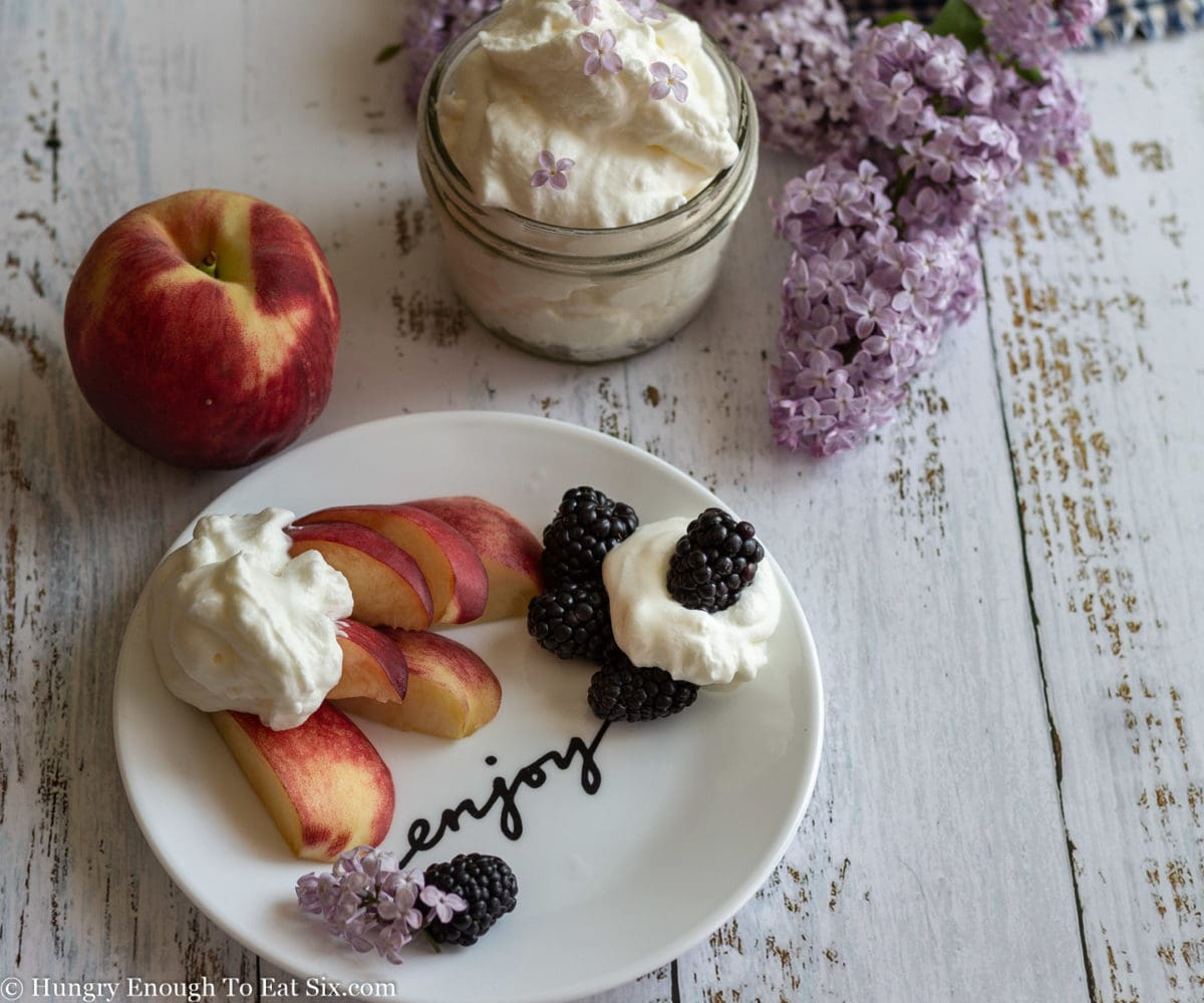 Sliced peaches and blackberris with whipped cream on a white plate, with a whole peach in background.