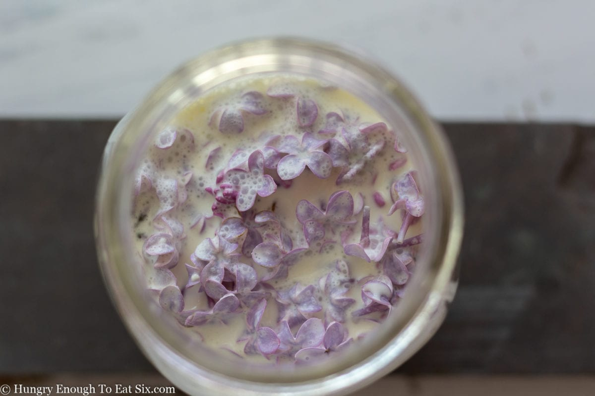 Glass jar full of cream with lilac flowers submerged in the cream.