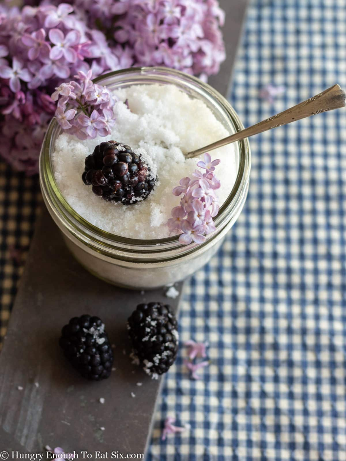 White lilac scented sugar in a glass dish with lilac blooms and fresh blackberries.