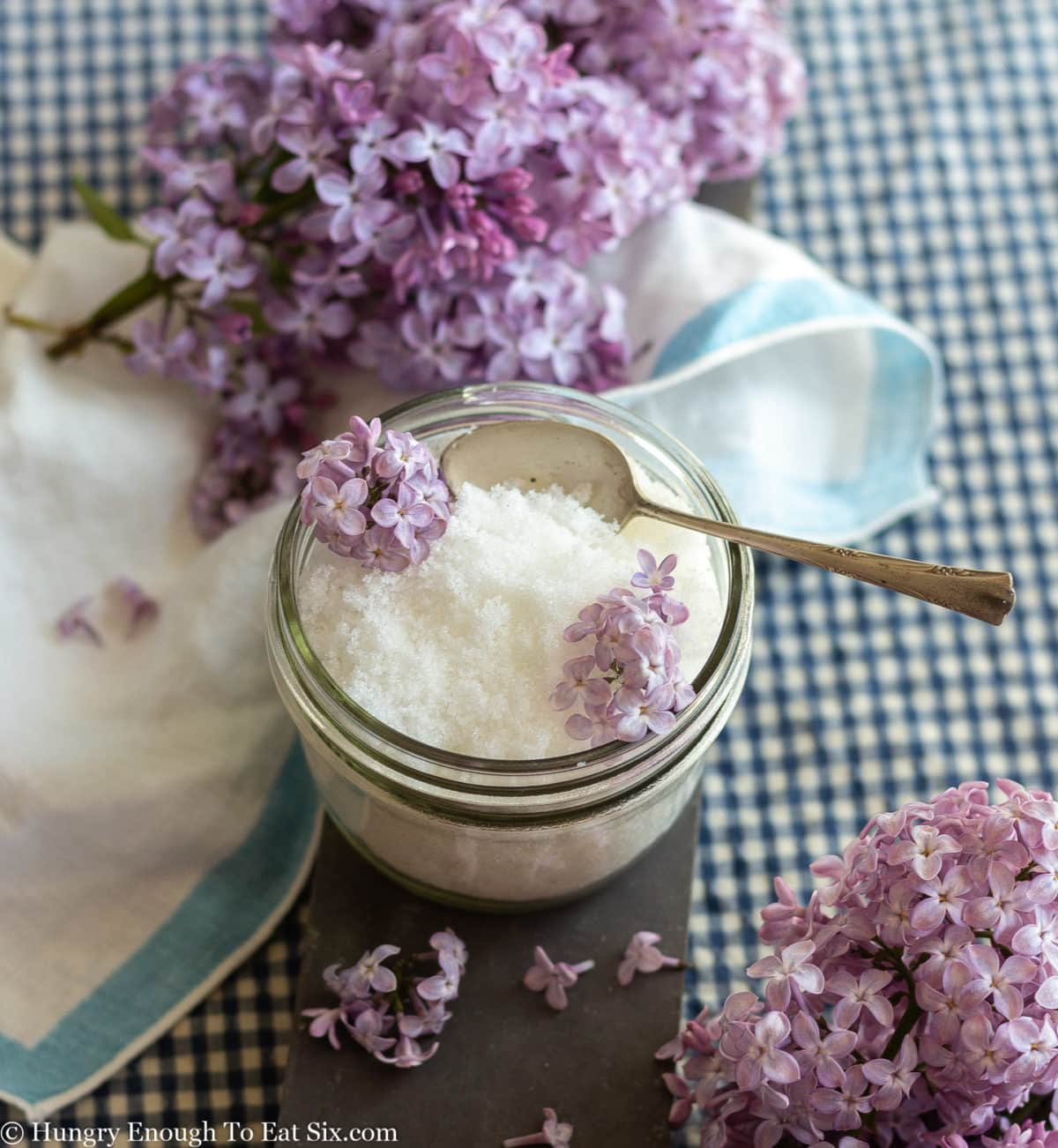 Blue and white linen around a glass bowl of white sugar, and purple lilacs scattered around.