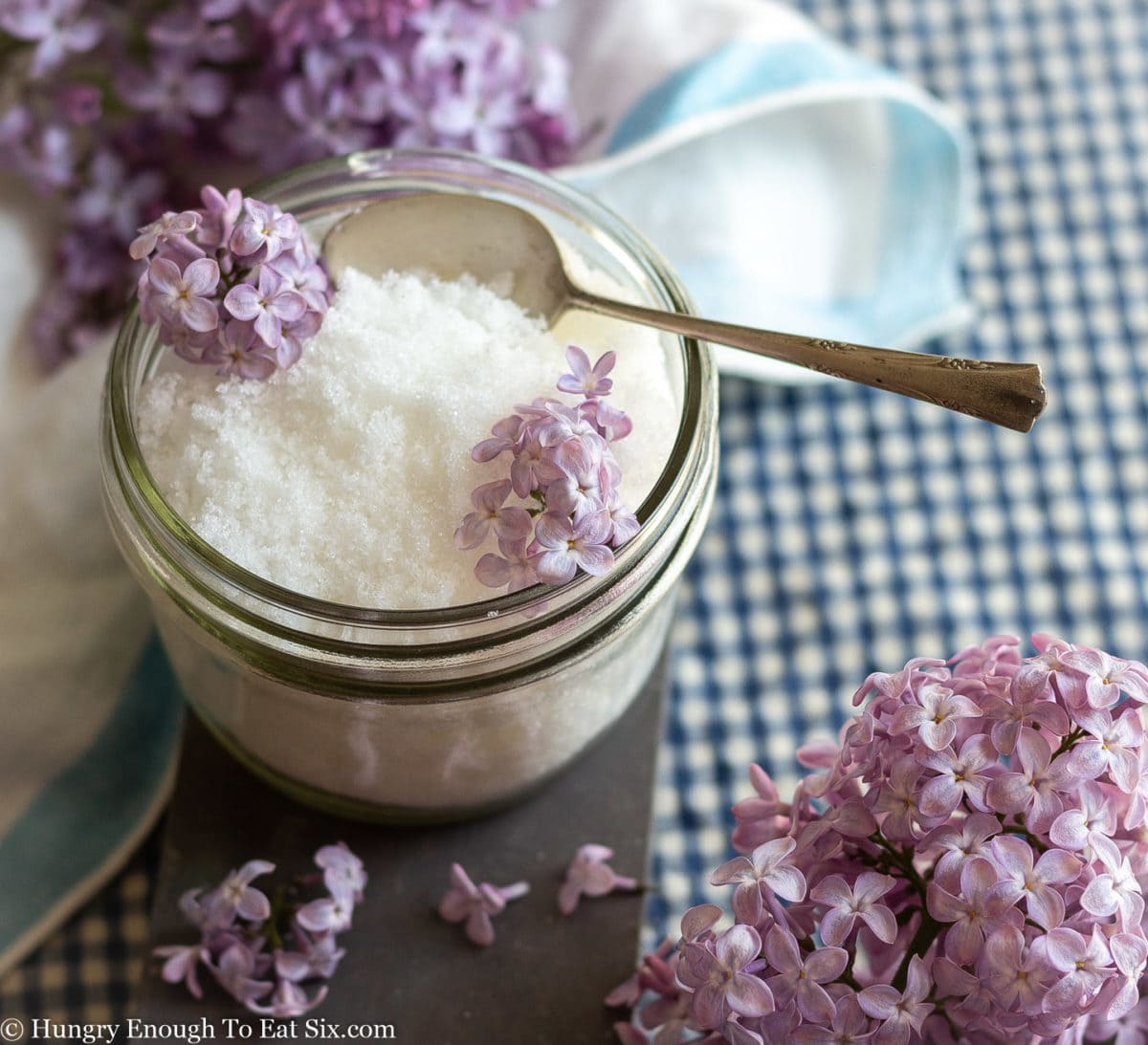 Blue checked tablecloth under a glass bowl of white sugar and purple lilac blooms.