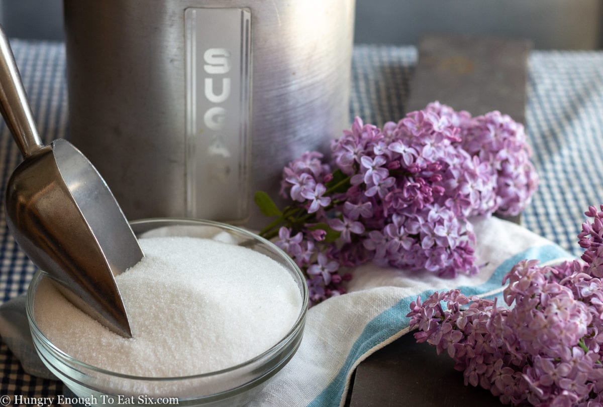 A sugar canister behind a glass bowl of sugar and a scoop, plus purple lilac flowers.