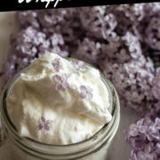 Lilac flavored whipped cream in a mason jar and lilacs behind.