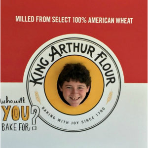 King Arthur Flour white and red billboard with a hold in center, boy's head poking through.