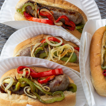 Four Buns holding sausage and grilled peppers and onions.
