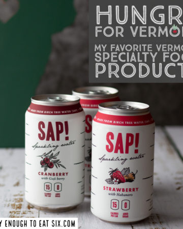Three cans of Sap! sparkling water on a white wooden surface