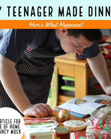 Teenage male in tshirt and apron reading cookbook on table