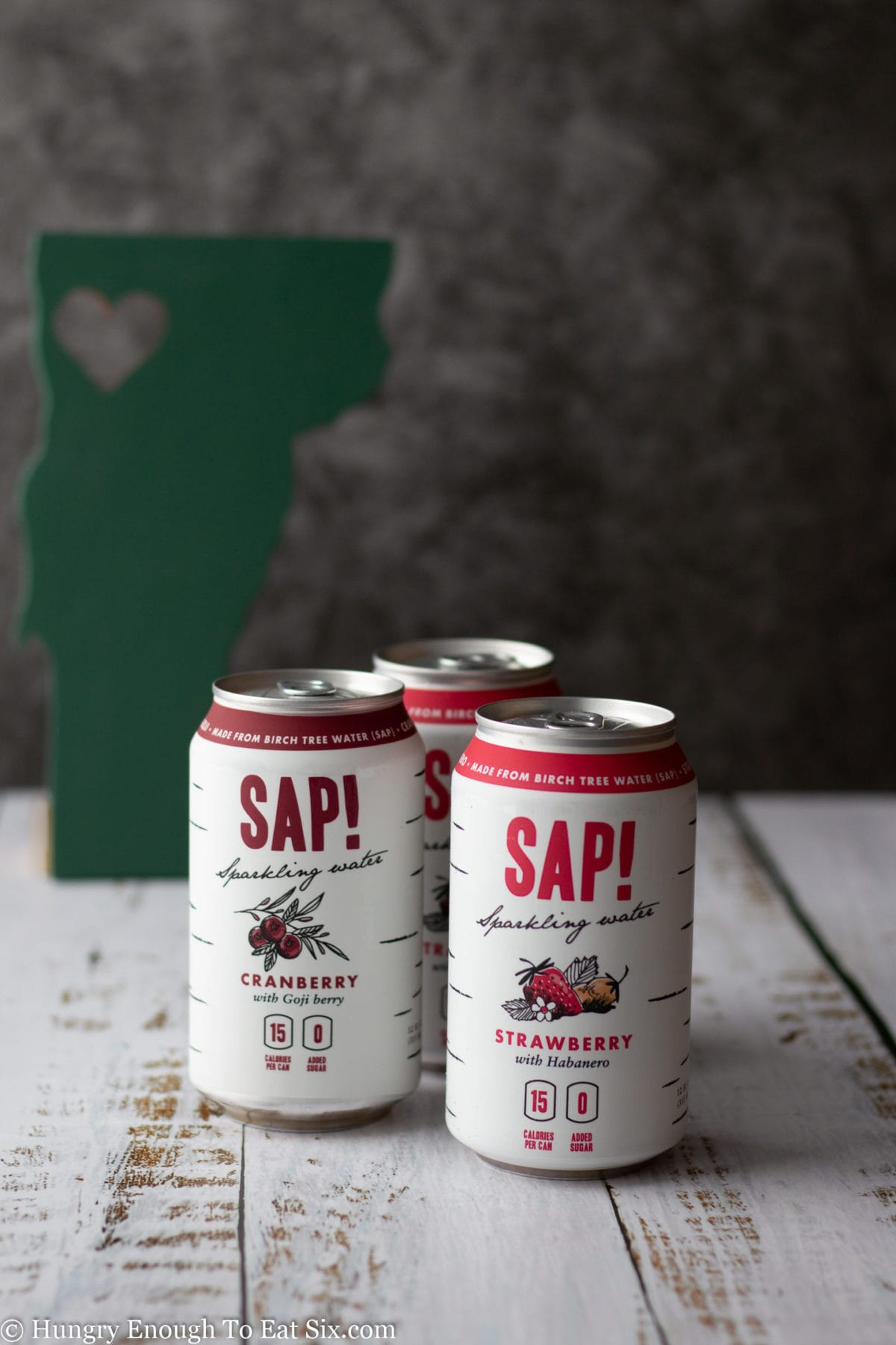 Cans of Sap! sparkling water with an image of the state of Vermont in background