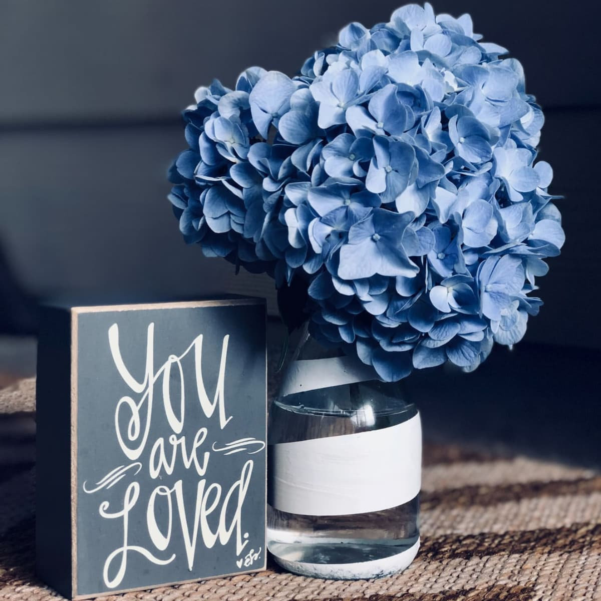 Blue hydrangea in a white striped vase next to a sign.