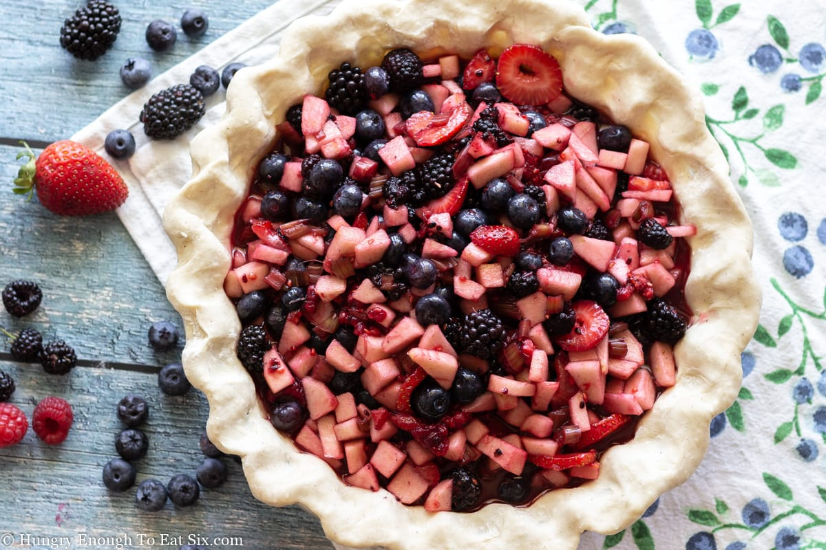Fruit filling in pie shell with berries scattered nearby.