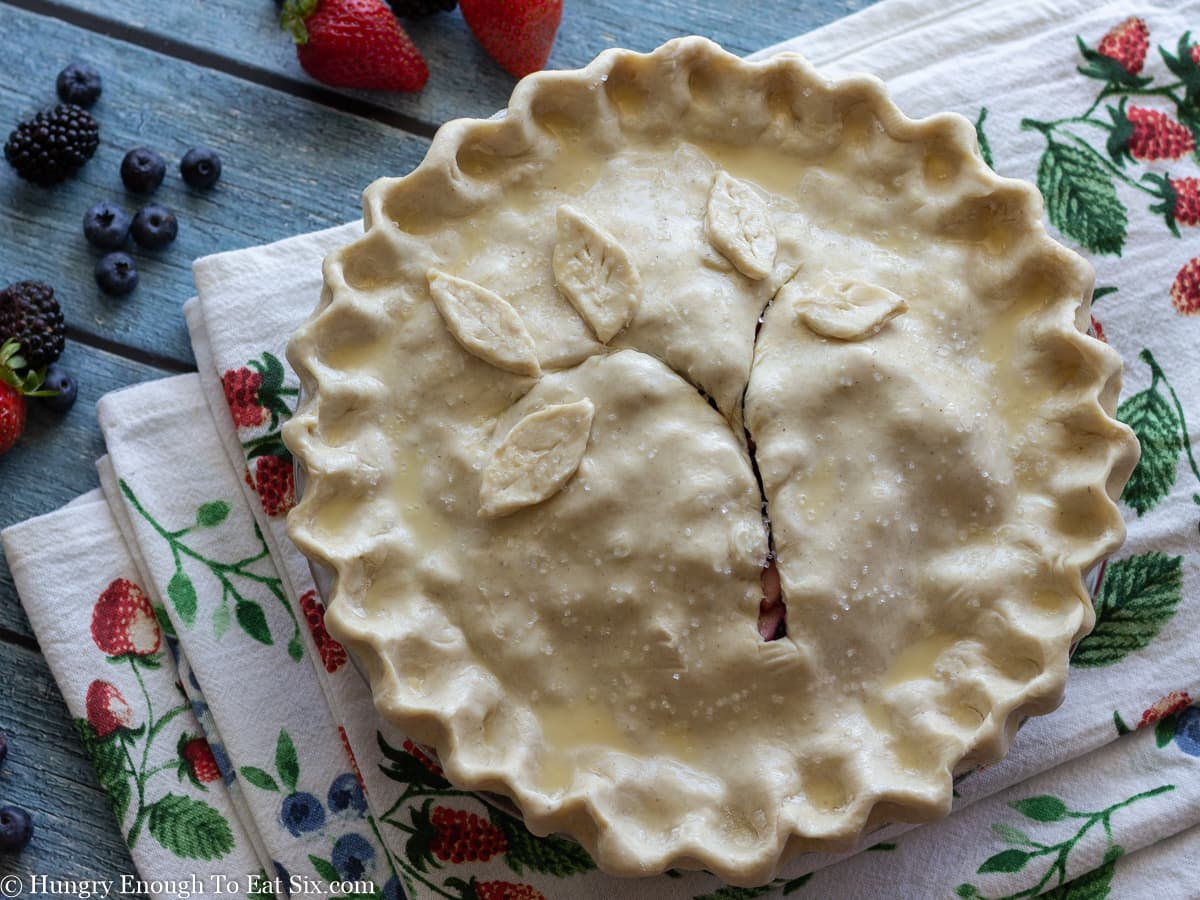 Unbaked berry pie topped with leaf cutouts and slashes.