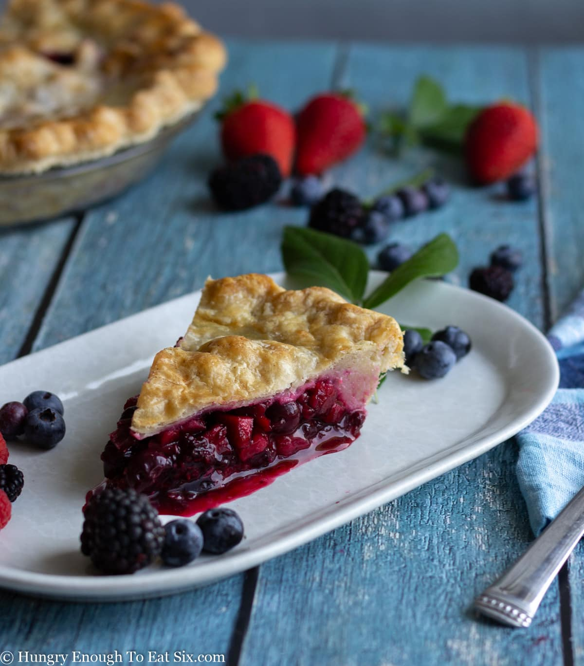 White oblong plate with slice of berry pie.