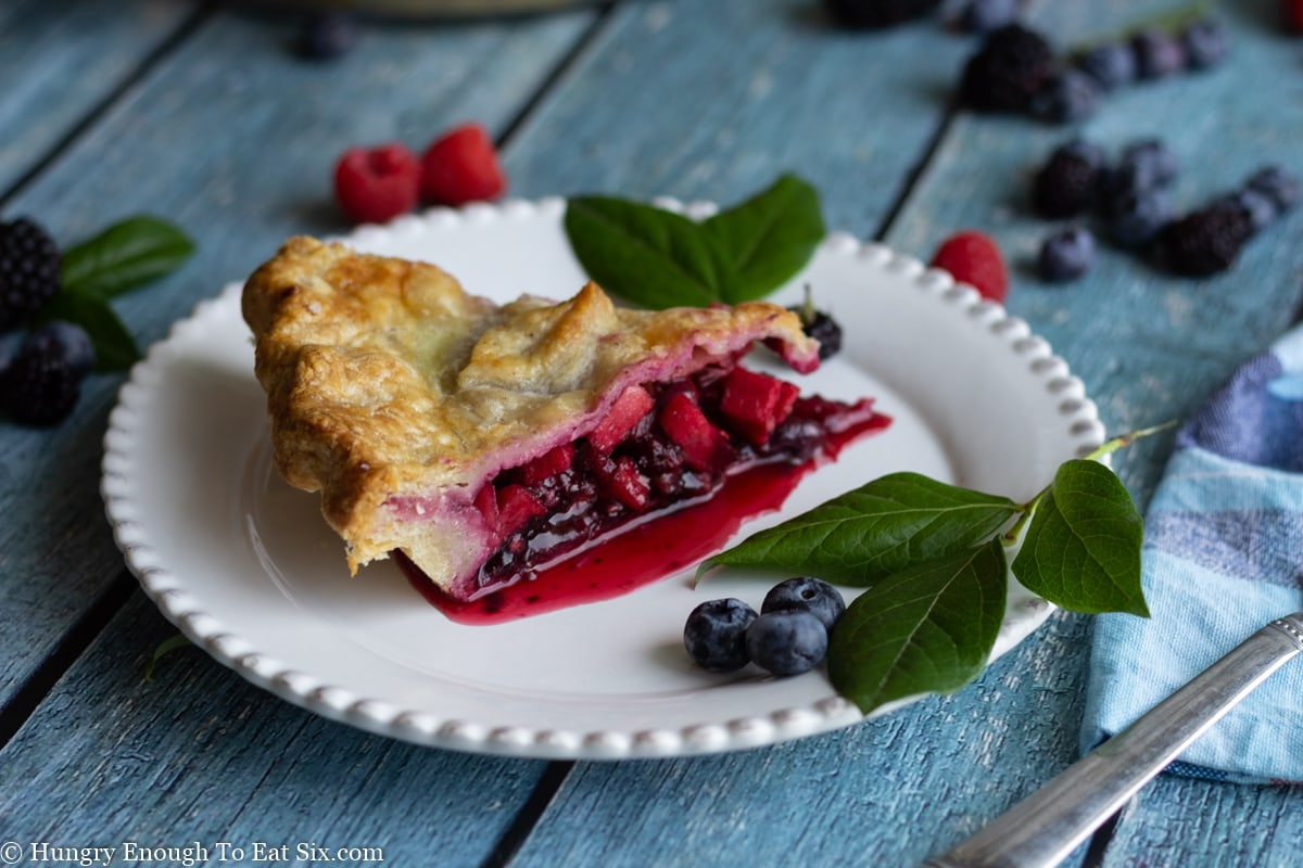 Red and blue berry filled pie with berries and leaves around.