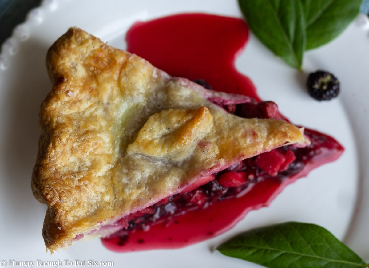 Berry pie with red juice flowing over white plate.
