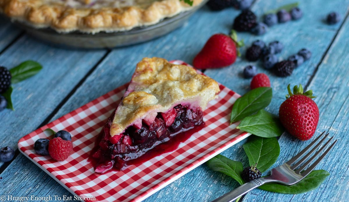 Red gingham plate with slice of berry pie.