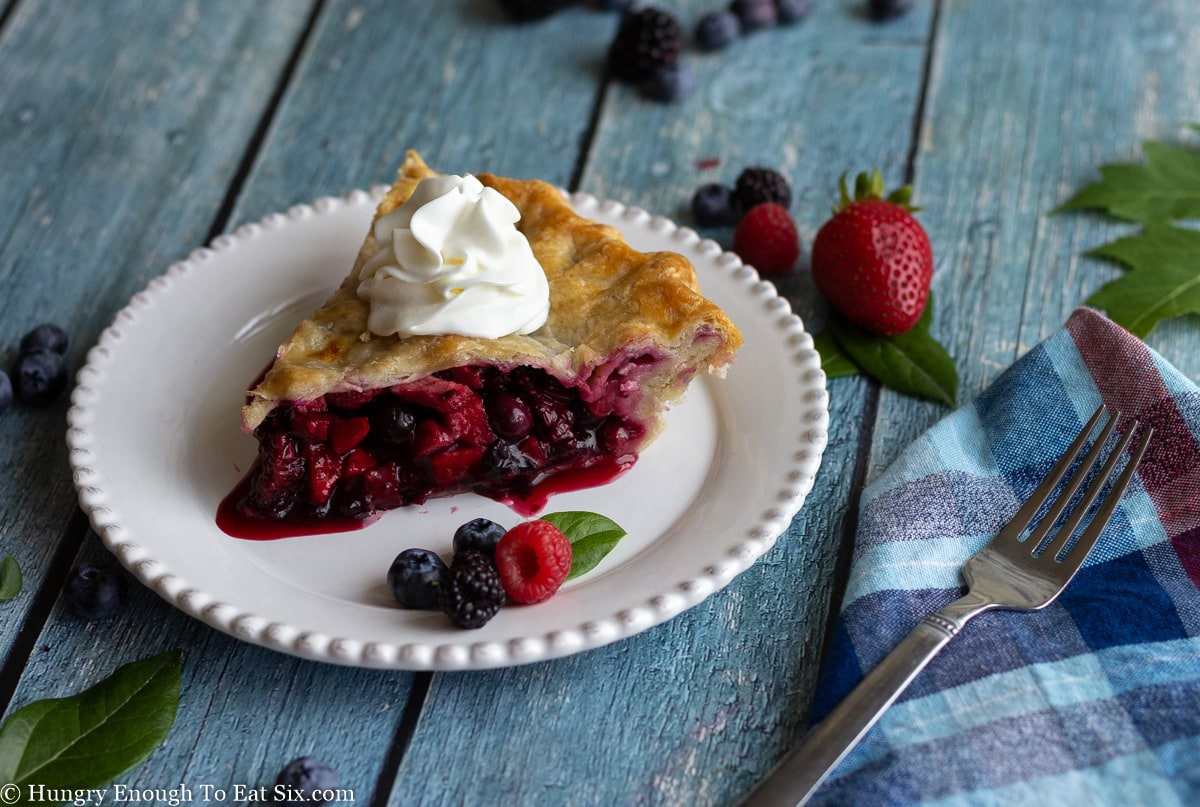 Blue wooden surface with berry pie on white plate.