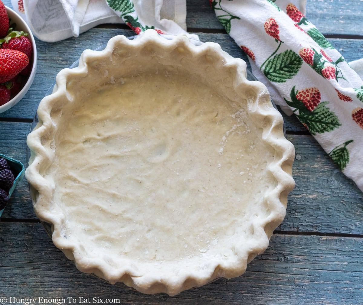 Crimped pie dough in a pie plate.