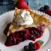 Slice of fruit pie on a white plate with whipped cream.