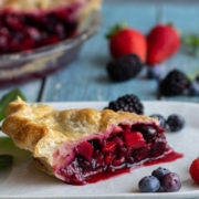 Slice of berry pie on a white plate with berries.
