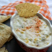 Oval bowl holding thick cheese and corn dip