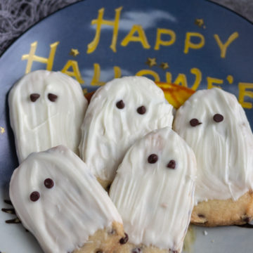 White chocolate ghost cookies laying on a Halloween decorative plate