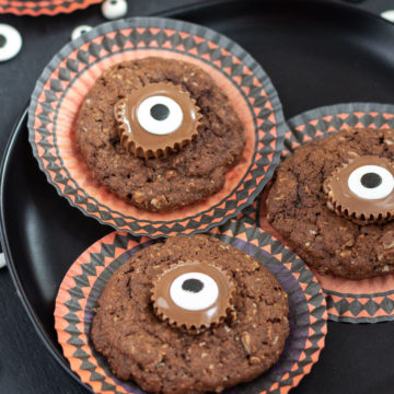 Round cupcake papers with chocolate cookies decorated with candy eyes