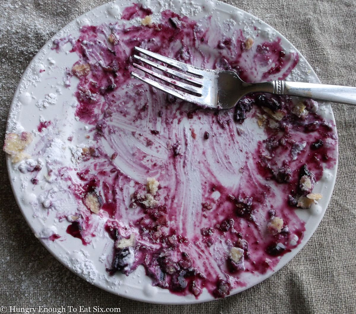 White plate with remains of blueberry sauce and pie crust crumbs, and a fork
