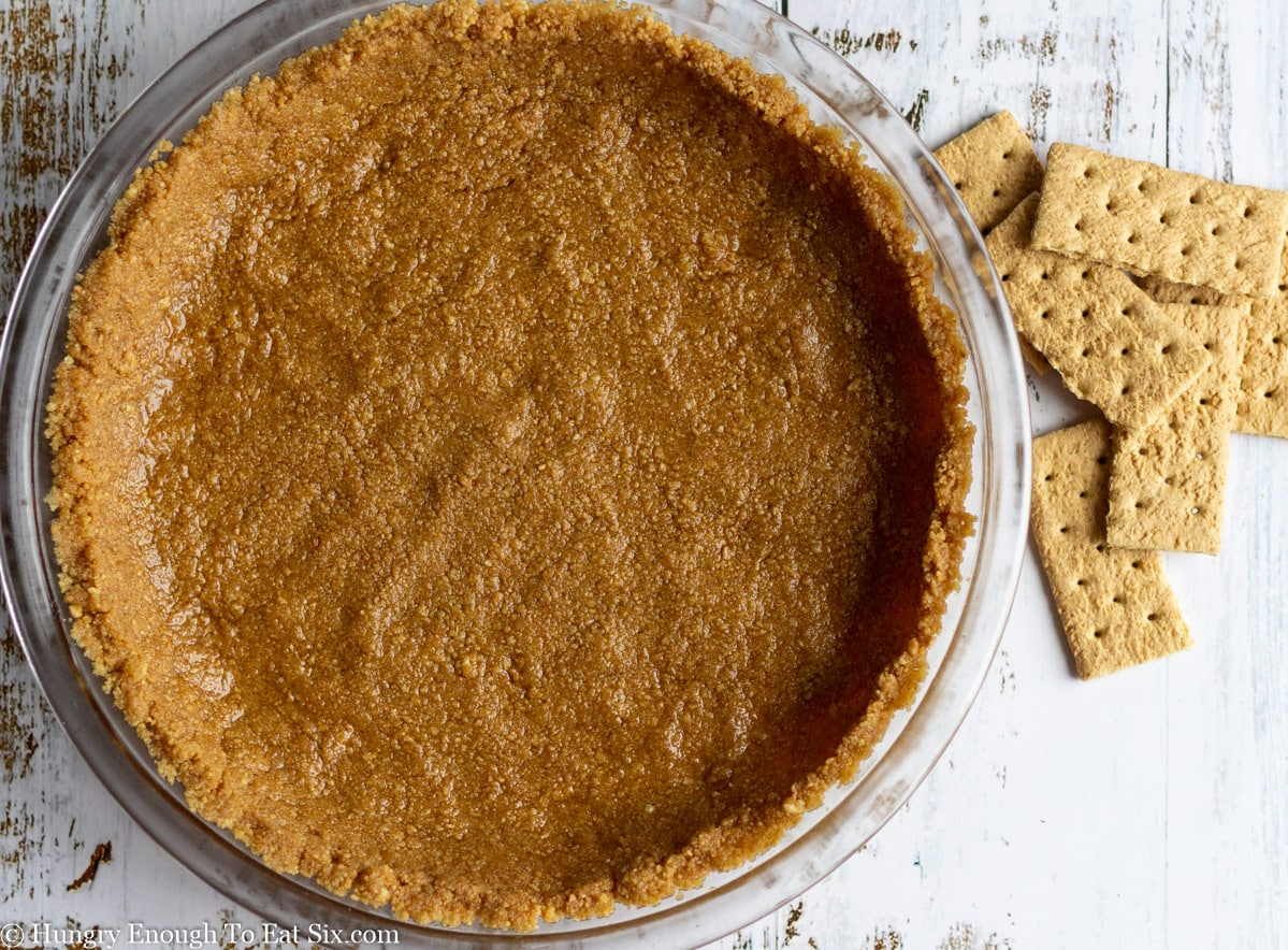 Wet graham cracker crumbs pressed in a pie plate