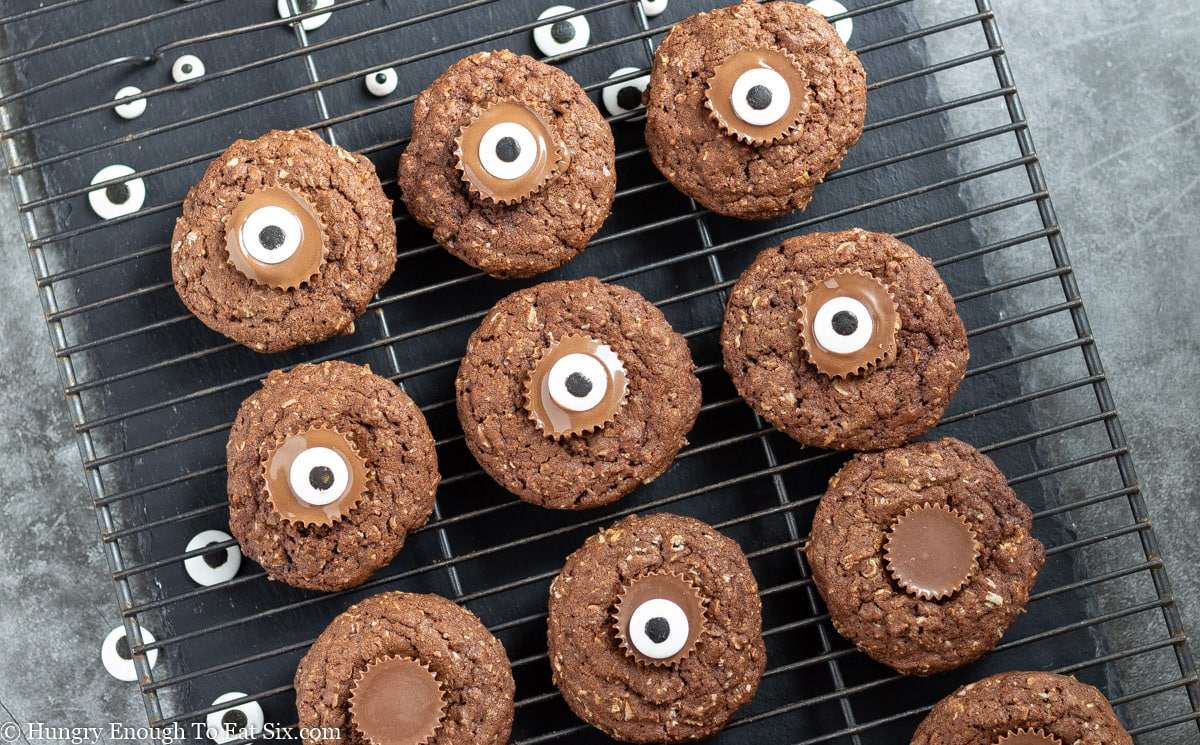 Cooling rack with chocolate cookies that have peanut butter cups and candies in the centers
