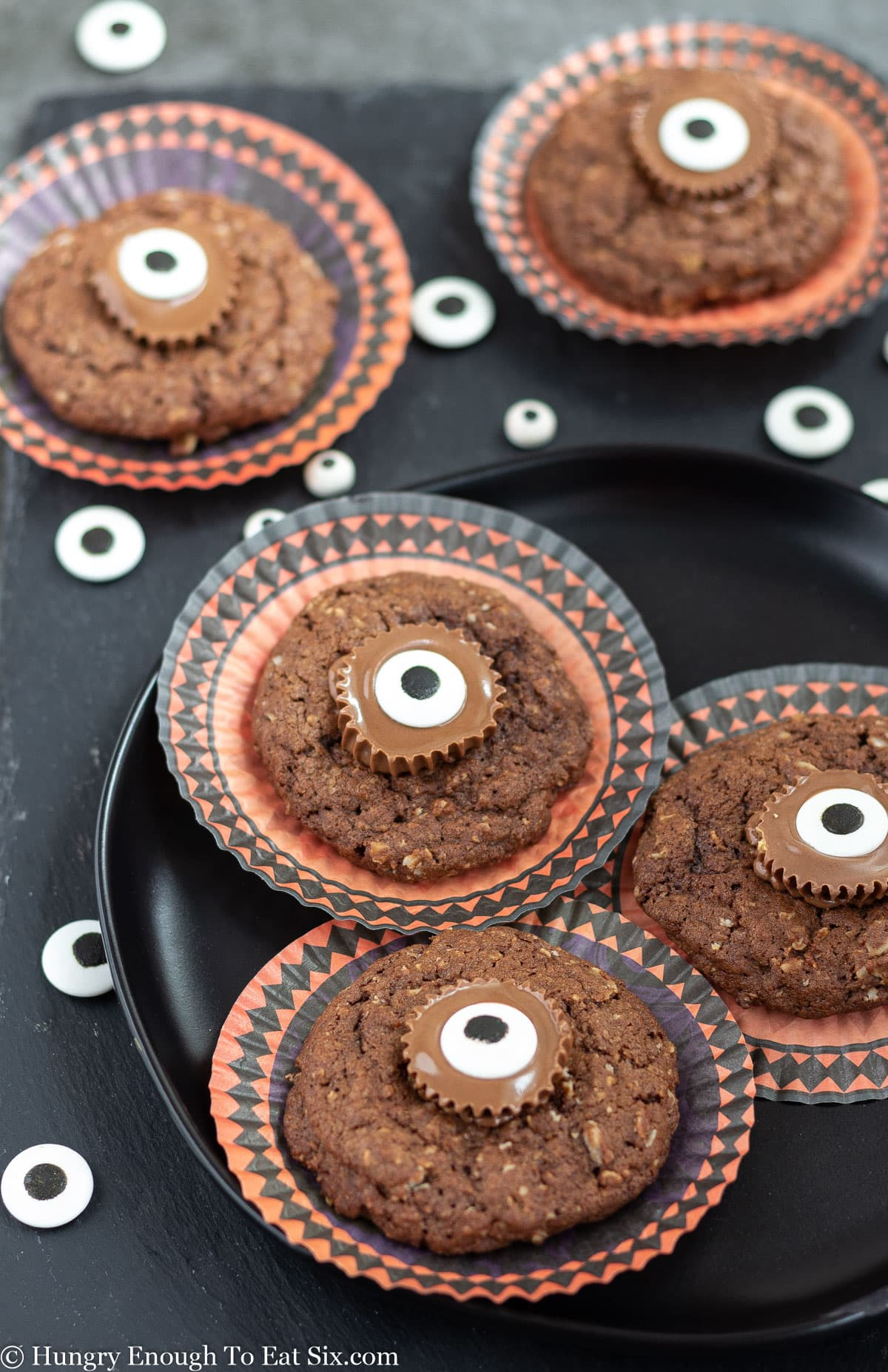 Chocolate cookies with peanut butter cup centers and candy eyes