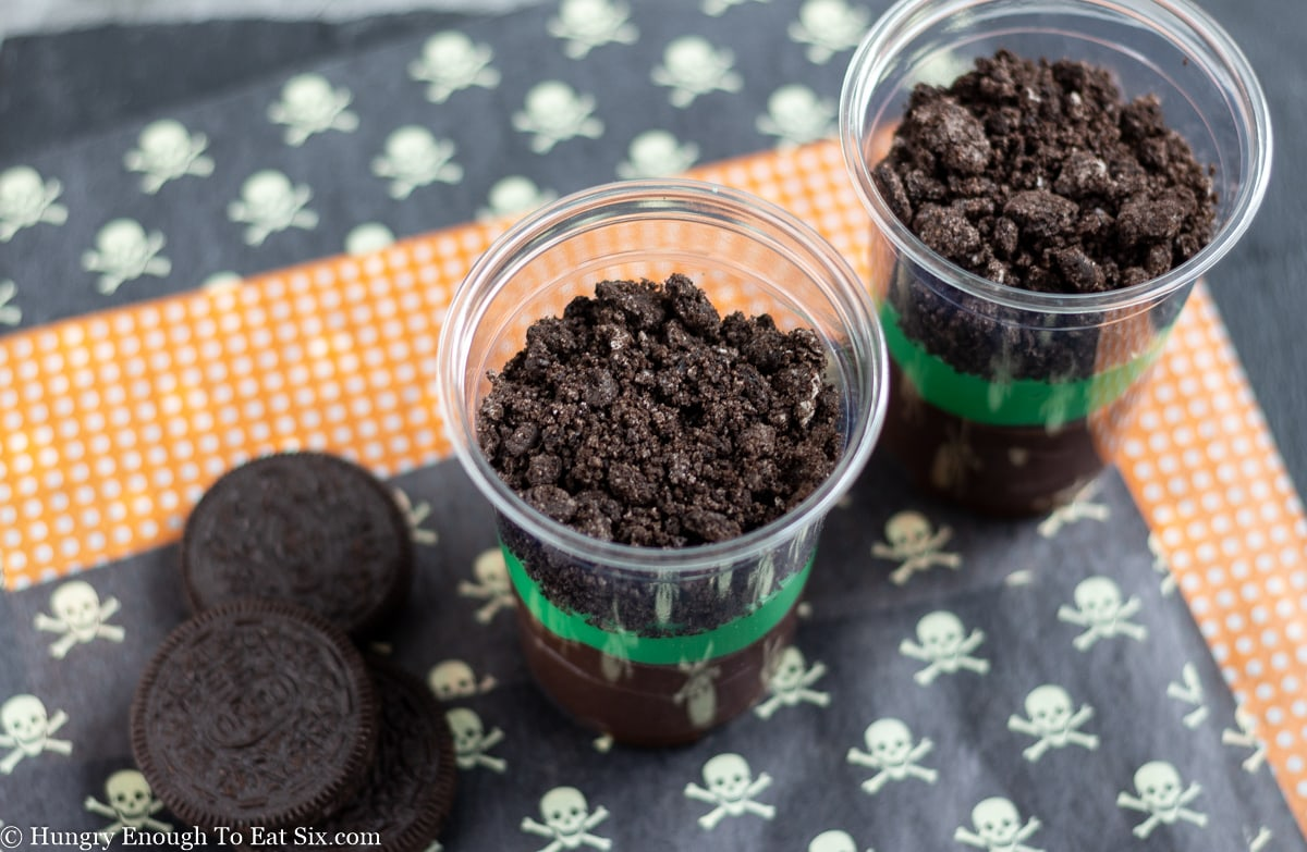 Crushed Oreo cookies in a clear cup over green pudding