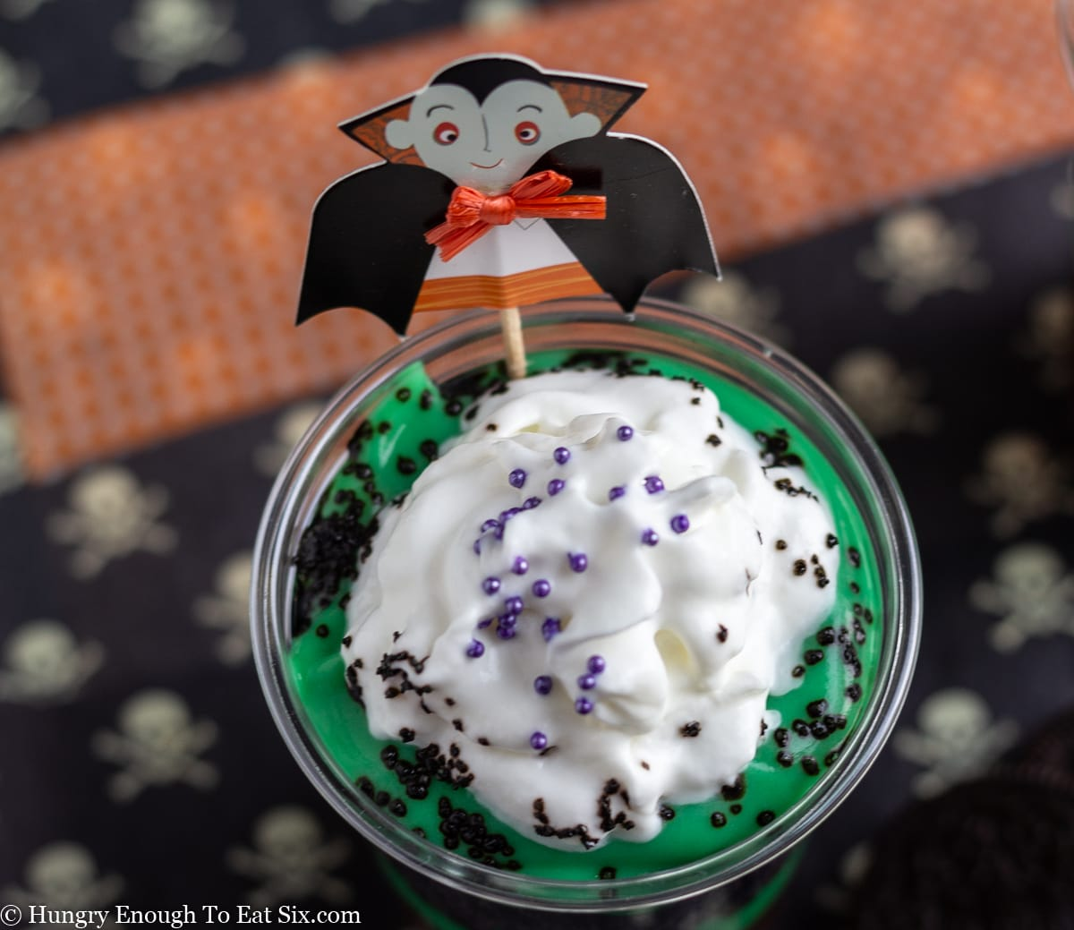 Top of a green and brown parfait with whipped cream topped with a vampire pick