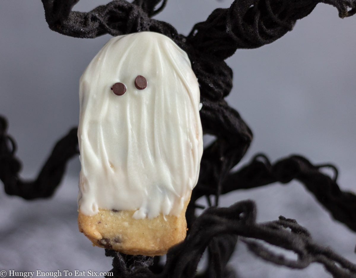 Small ghost shaped cookie next to a twisted wire tree