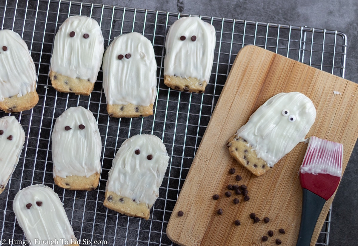 White oval cookies decorated like ghosts on a wire cooling rack
