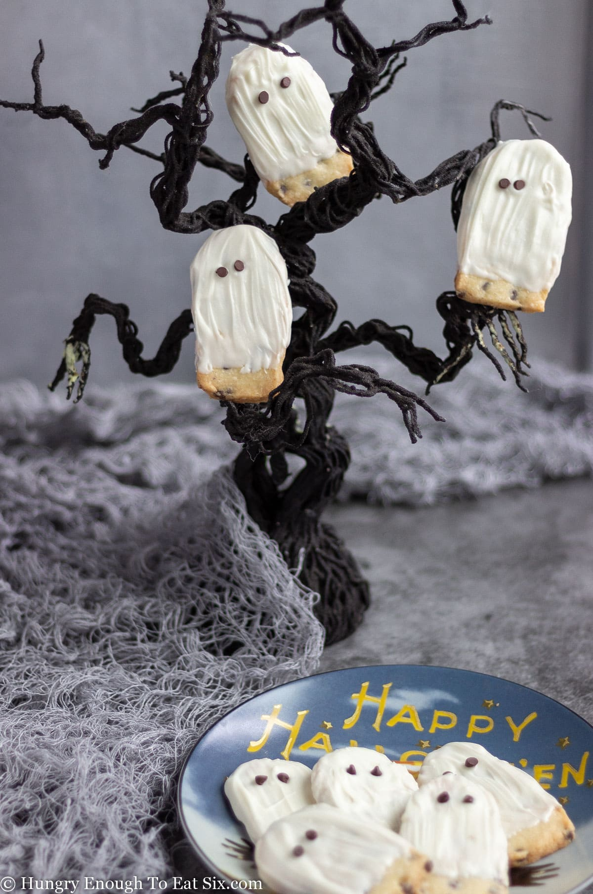 Ghost cookies arranged on a Halloween plate and in a wire tree