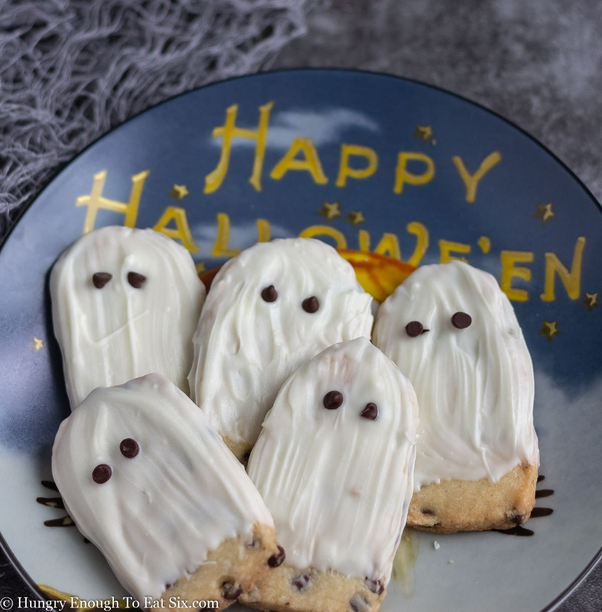 Halloween decorated plate holding 5 white ghost cookies