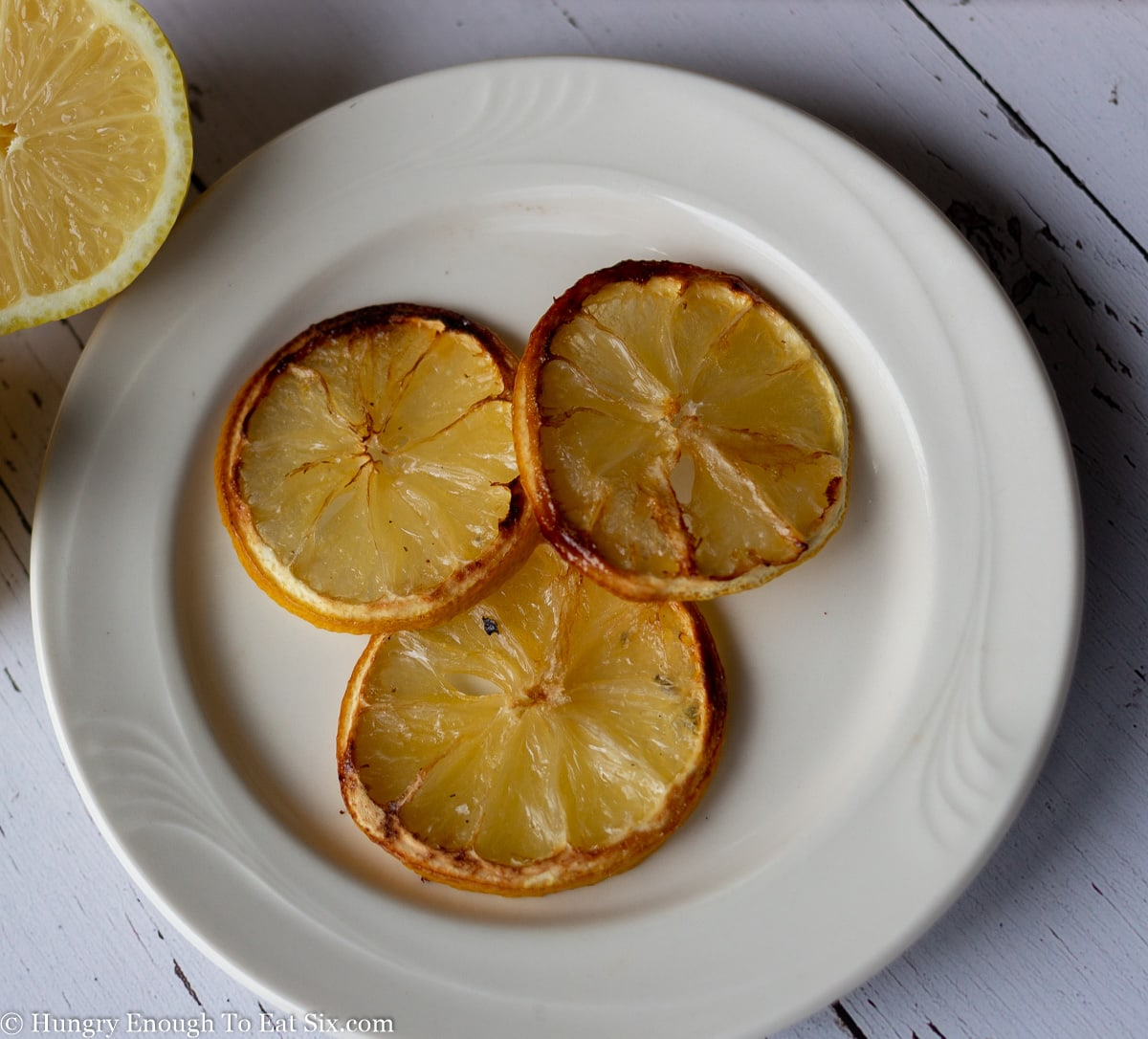 Three browned lemon slices on a white plate