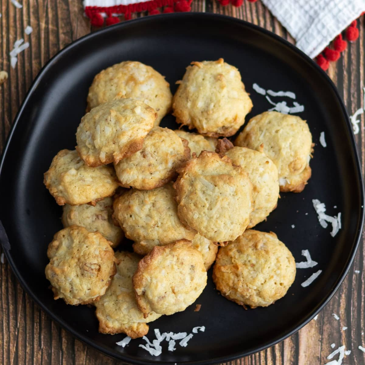 PIle of lightly browned cookies on a black plate