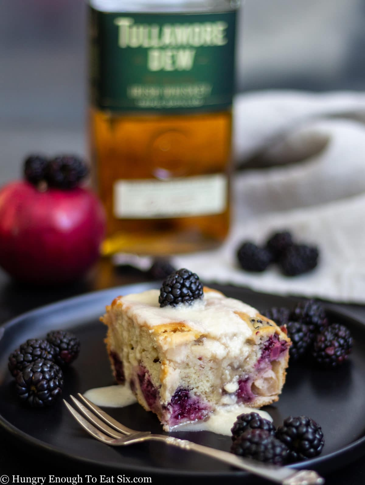 Berry filled cake slice on a plate with a bottle of whiskey in the background