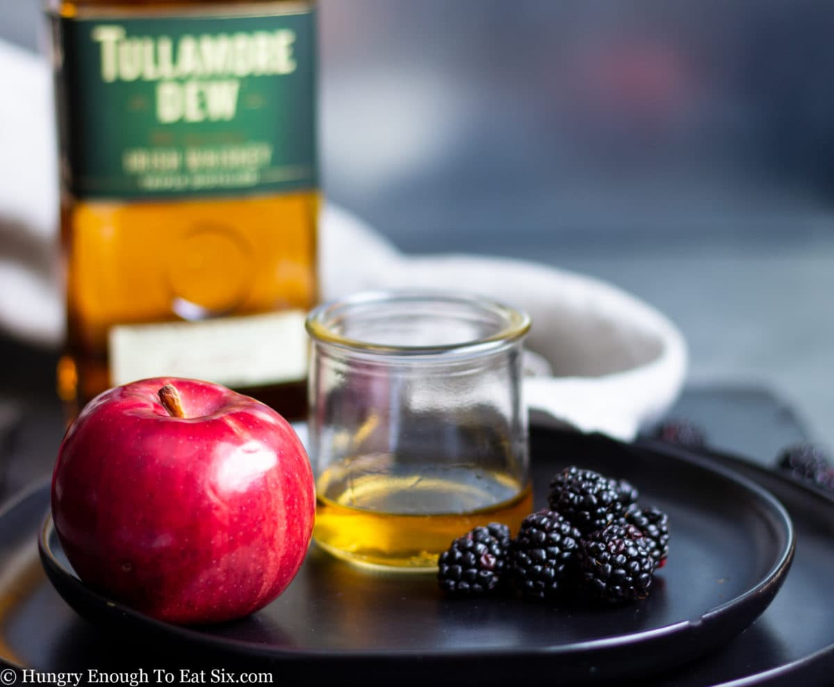 Bottle and glass of whiskey with fruit