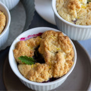 Cobbler with berries and a mint leaf