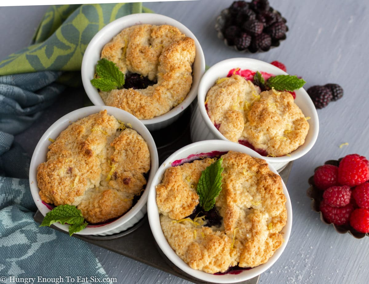 Four white cups with fruit and cobbler